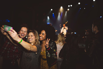 Playful, happy female millennial friends taking selfie with camera phone at music concert in nightclub