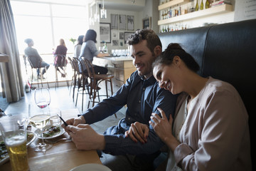 Affectionate young couple with smart phone at bar table
