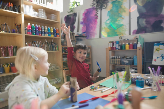 Eager preschool boy raising hand in art class
