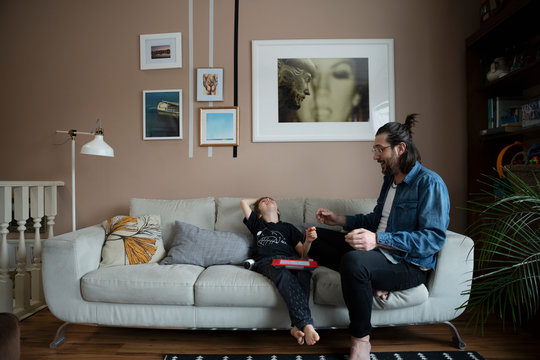 Father and son playing, laughing on living room sofa