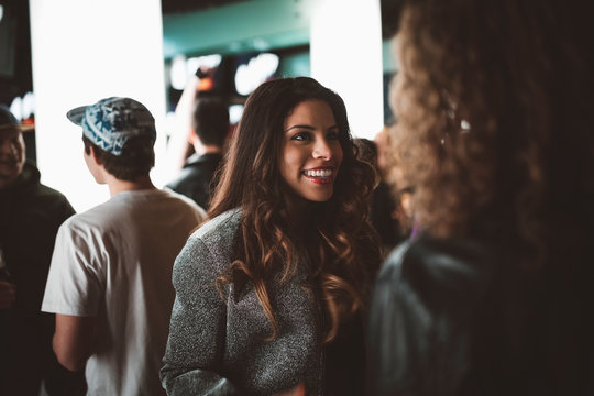 Smiling young female millennial talking with friends in bar