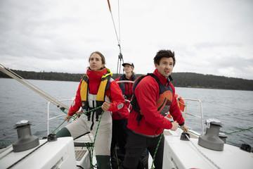 Focused sailing team adjusting rigging rope, training on sailboat on ocean