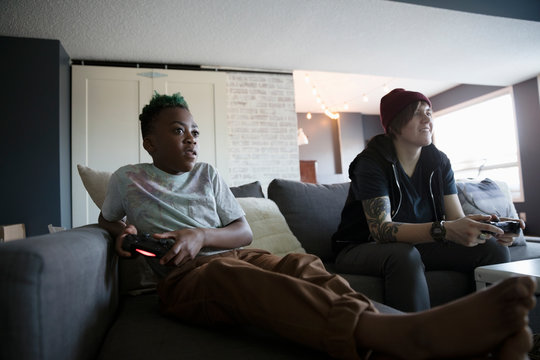 Babysitter and boy playing video game on sofa