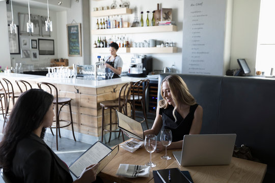 Businesswomen looking at menu at working lunch in cafe