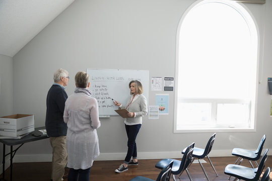 Woman at whiteboard leading grief counseling support group in community center