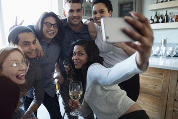 Playful young friends with camera phone taking selfie, enjoying happy hour, drinking wine