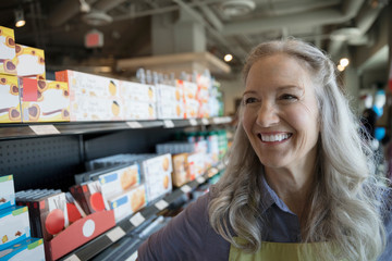 Portrait confident, smiling female senior worker in grocery store aisle
