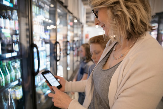 Mother with smart phone list grocery shopping in refrigerated market aisle