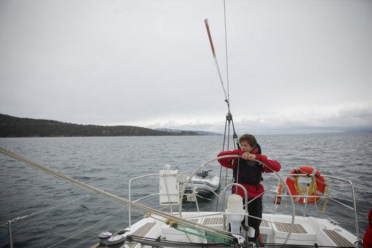 Teenage boy leaning on steering wheel on sailboat on ocean