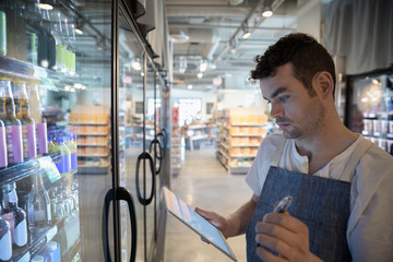 Male worker with digital tablet taking inventory at refrigerated case in grocery store