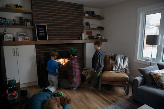 Father and sons building fire in living room fireplace