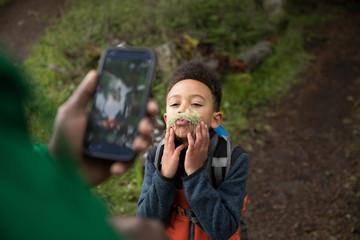 Playful boy posing with fake moss mustache