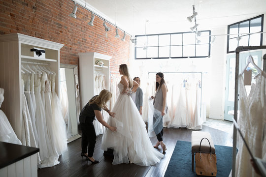 Bride and friends at wedding dress fitting in bridal boutique