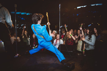 Crowd cheering for enthusiastic rockabilly musician doing the splits on stage at music concert in nightclub Fotobehang