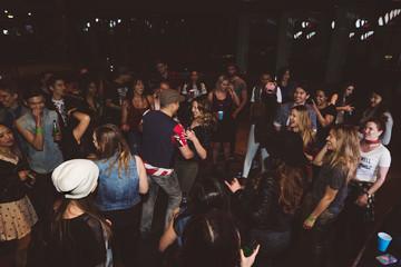 Milennials dancing and partying on nightclub dance floor