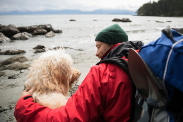 Man and dog backpacking on rugged beach