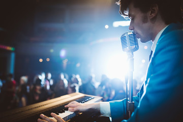 Rockabilly musician playing electric piano and singing into microphone on stage at music concert