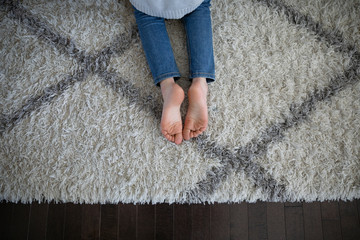 View from above girl with bare feet laying on rug