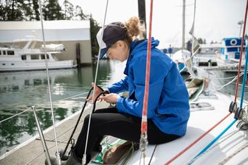 Smiling woman adjusting rigging on sailboat