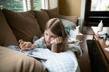 Sick girl using digital tablet on living room sofa