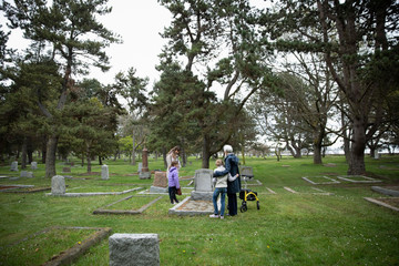 Multi-generation women visiting gravesite in cemetery Fototapete