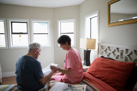 Home caregiver explaining paperwork to senior men in bedroom