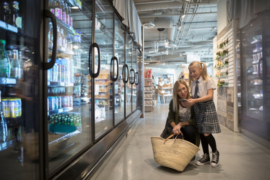 Mother and daughter with smart phone grocery shopping in refrigerated market aisle