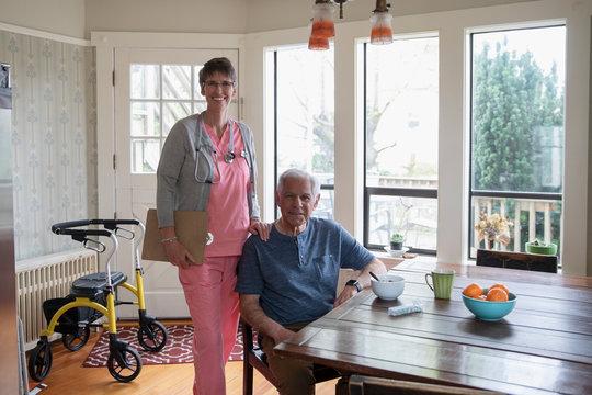 Portrait confident home caregiver and senior man at kitchen table