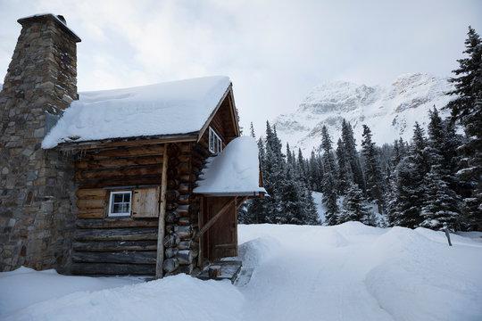 Snowy cabin below mountains