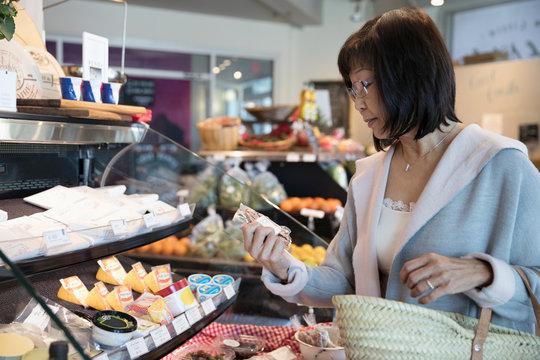 Senior woman browsing deli display in grocery store