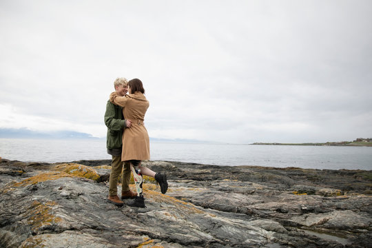 Young woman amputee hugging boyfriend on craggy beach
