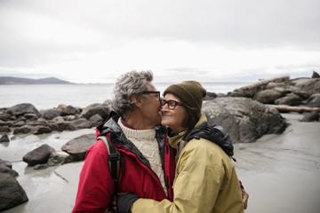 Affectionate active senior couple hugging on rugged beach