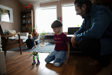 Father watching son playing with robot toy on living room floor
