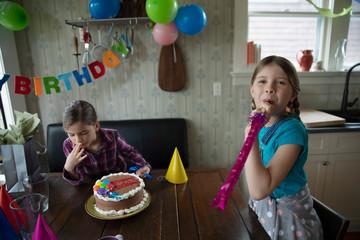 Portrait playful sisters celebrating birthday party