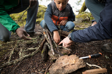 Trail guide and father helping boy build a fire in woods