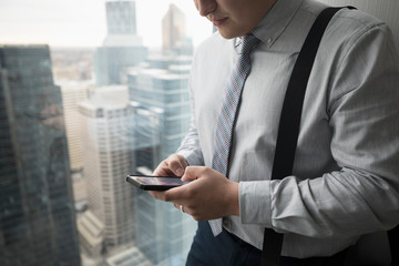 Senior businessman using smart phone at urban office window
