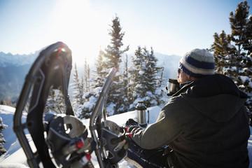 Solo traveler snowshoer taking a break, drinking coffee on sunny, idyllic mountain