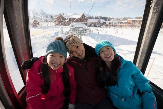 Portrait sister skiers riding gondola