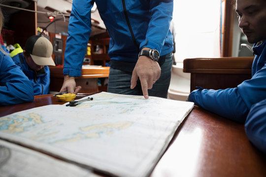 Sailing team plotting course at map on sailboat