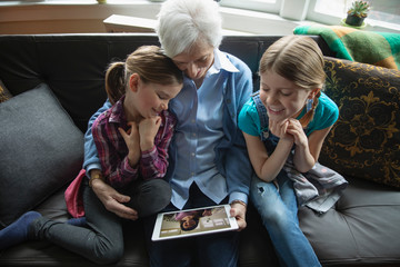 Grandmother and granddaughters video chatting with digital tablet on sofa