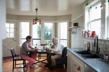 Home caregiver and senior man playing cribbage at kitchen table