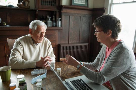 Home caregiver explaining prescription medication to senior man at dining table