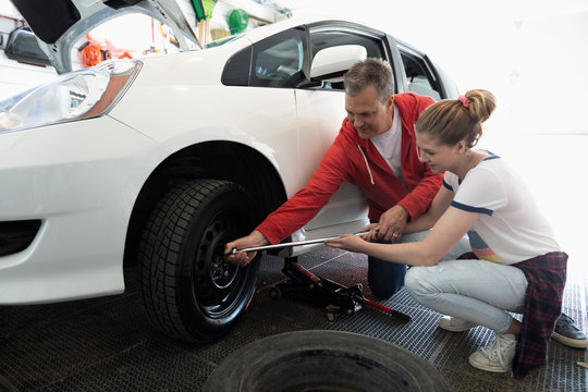 Father teaching tween daughter how to change car tire in garage