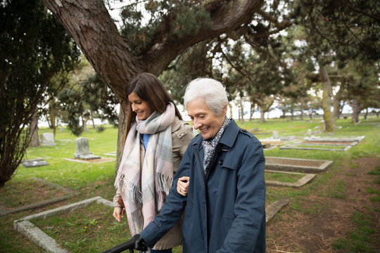Daughter walking with senior mother in cemetery