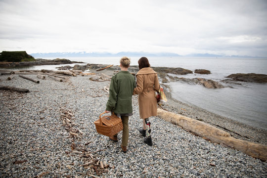 Young amputee woman walking with boyfriend carrying picnic basket on beach