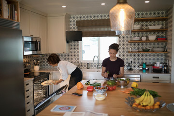 Mother and daughter cooking, preparing pizza and salad in kitchen