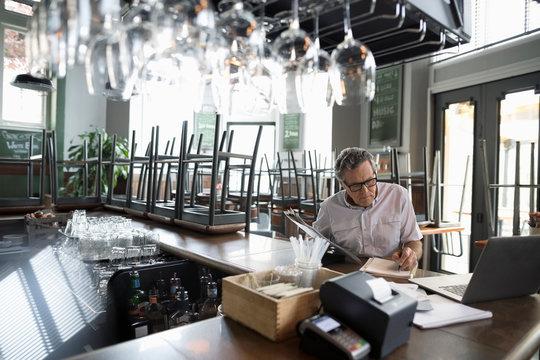 Senior restaurant owner doing paperwork