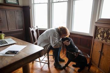 Affectionate woman kissing seeing eye dog