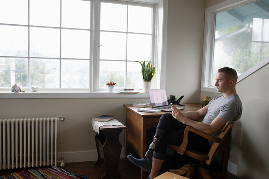 Young male amputee working at desk, using smart phone in home office
