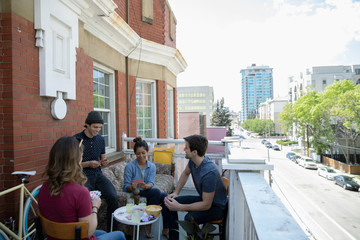 Millennial friends playing cards on urban apartment balcony
